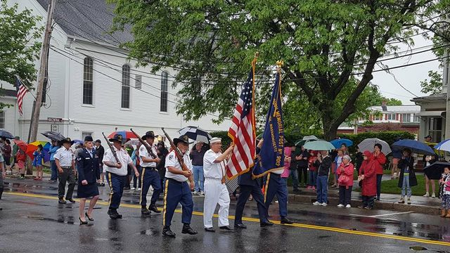 Group of veterans marching in Memorial day parade - 2 in front holding American flag and Post flag