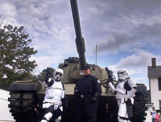 Men in star wars uniforms posing around tank