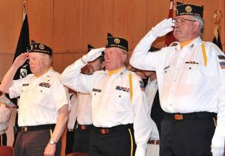 3 veterans saluting, faces somber